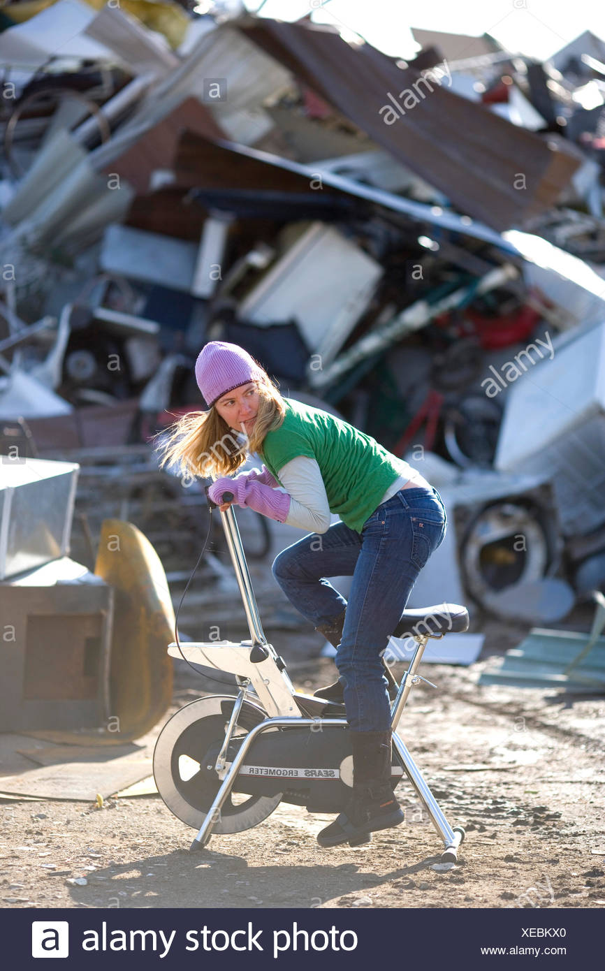 Adult woman riding a junked stationary bike in front of a scrap metal pile - Stock Image