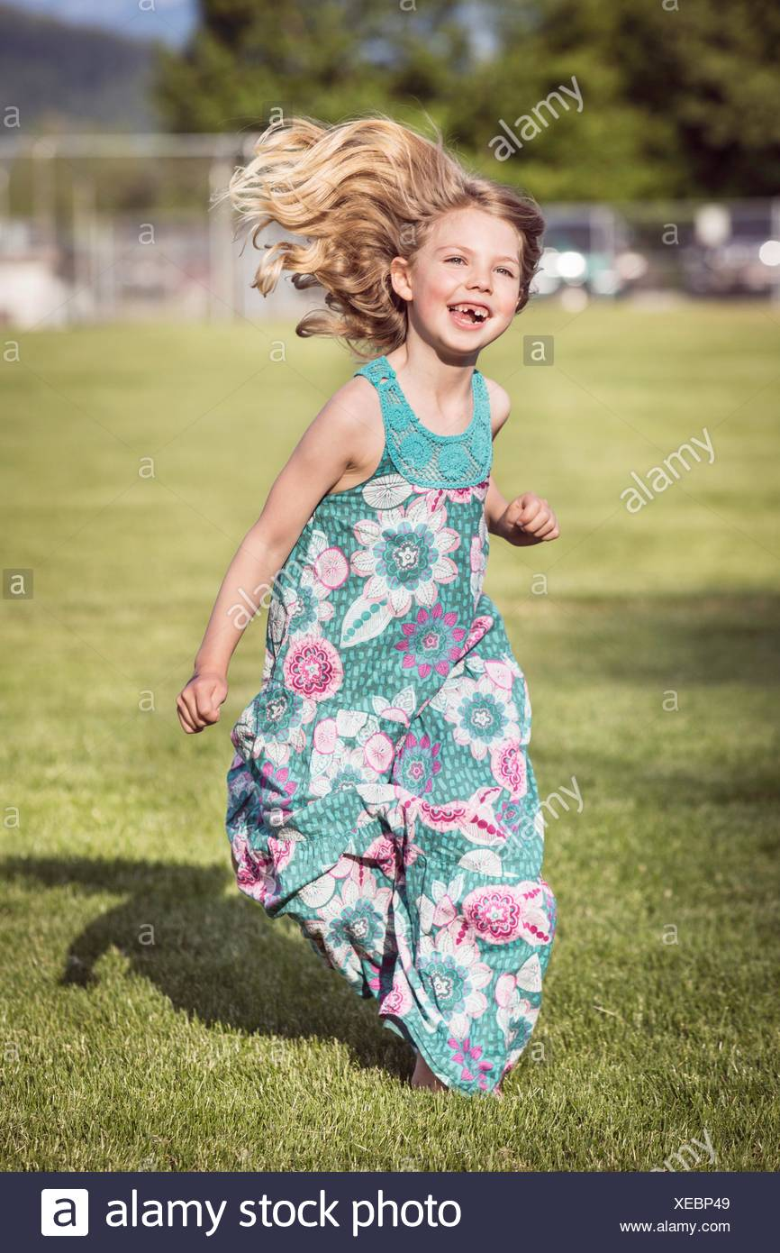 Girl wearing sundress running - Stock Image