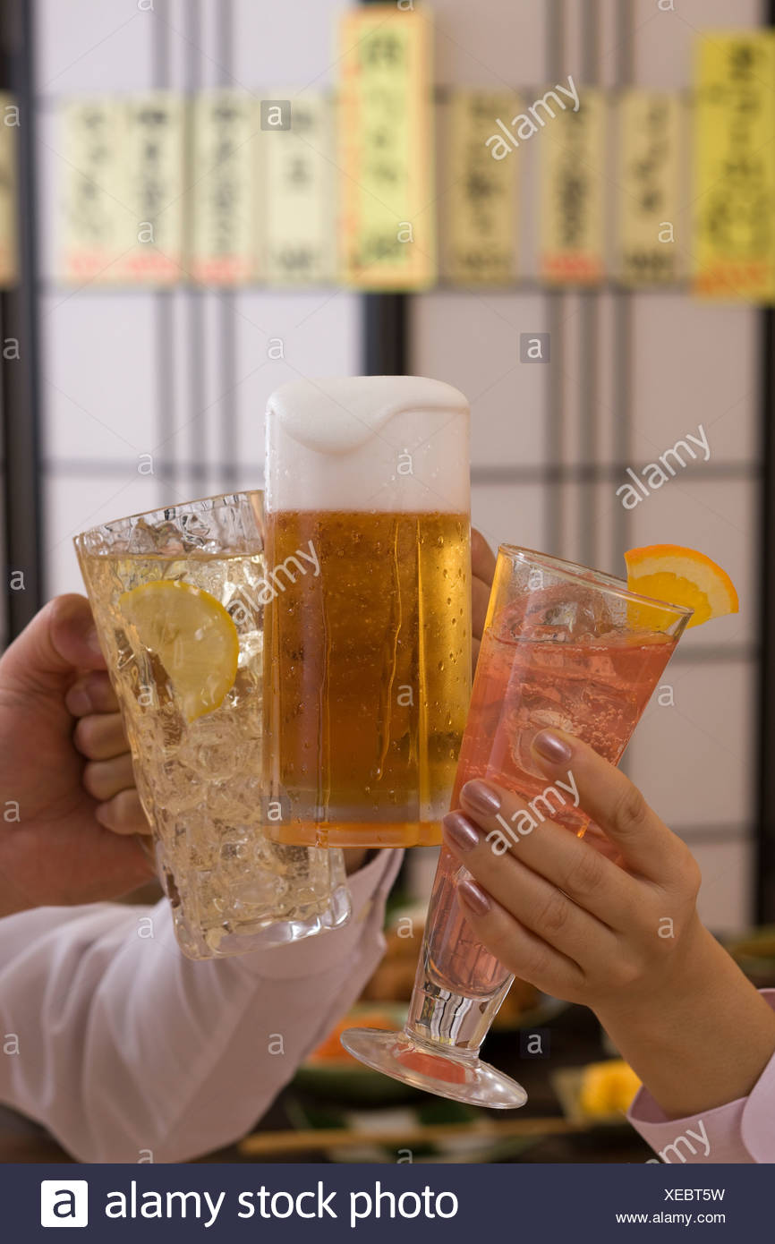 Three People Toasting with Each Other With Various Drinks at Izakaya Stock Photo