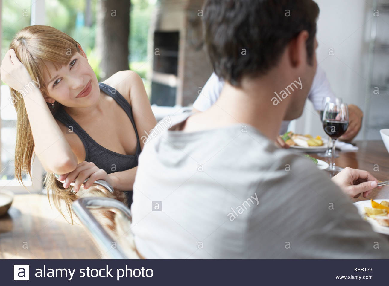 three people at dinner table focussing on one woman smiling - Stock Image