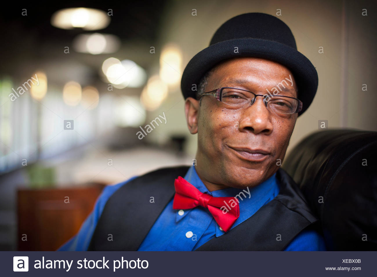 An african american man wearing a hat, vest and a red bow tie looks forward. - Stock Image