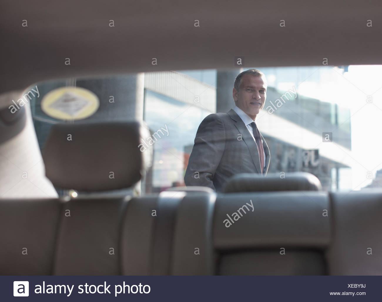 Businessman walking past car - Stock Image