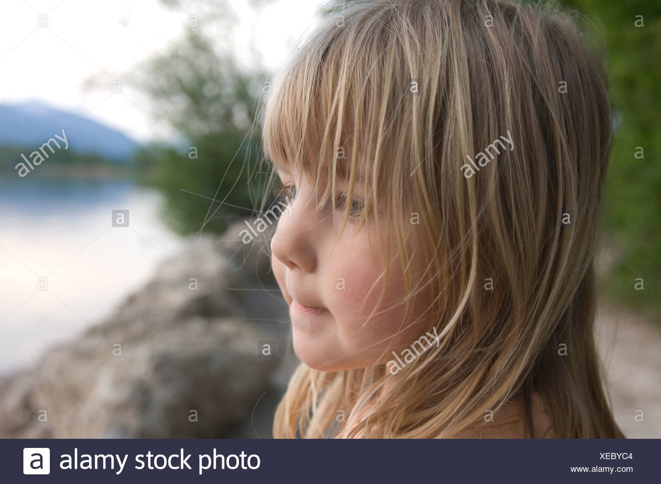 headshot of young girl standing on riverbank - Stock Image