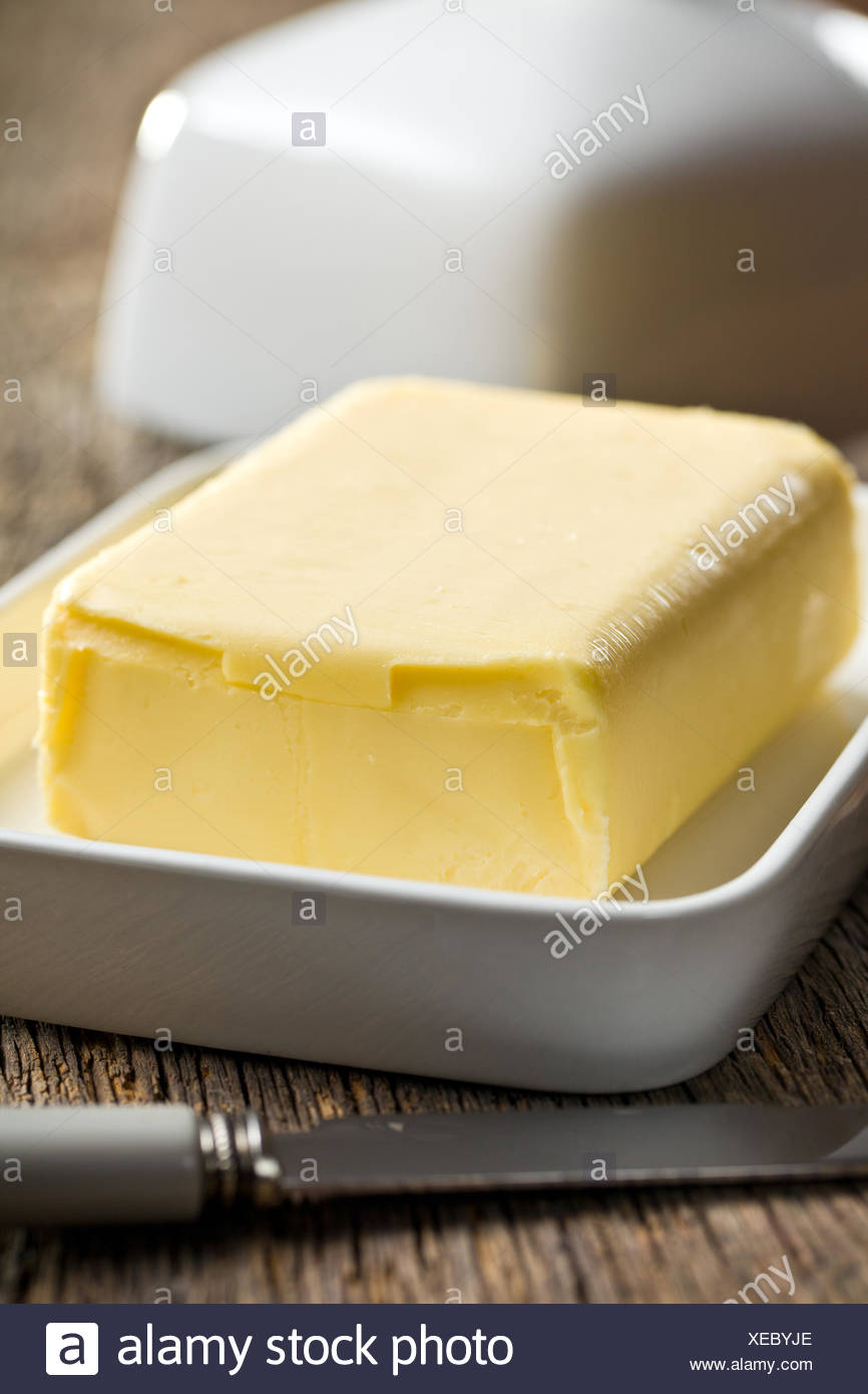 cube of butter with knife on wooden background Stock Photo