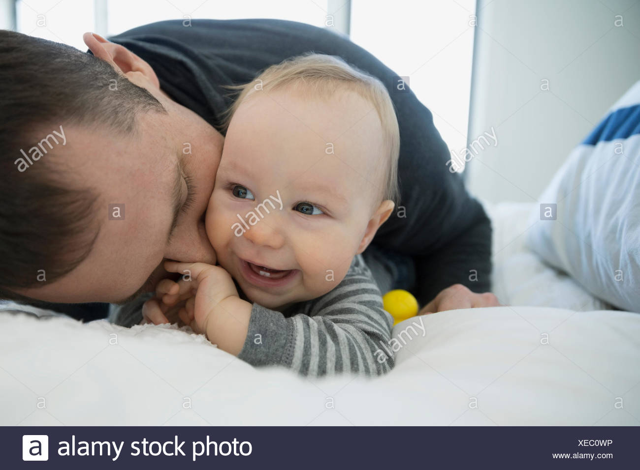 Father kissing smiling baby boy on bed - Stock Image