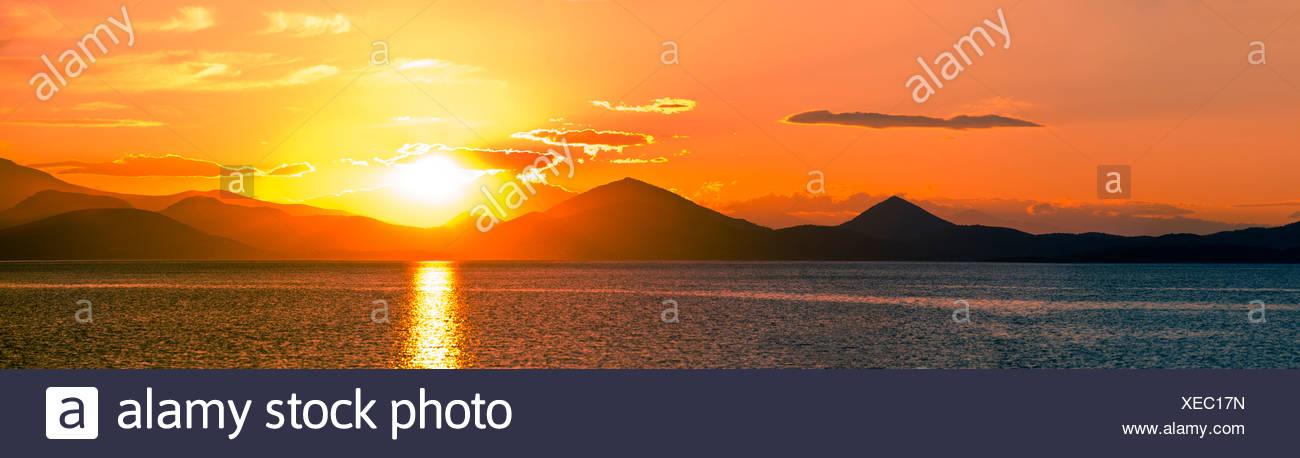 Panoramic shot of scenic sunset over Aegean sea - Stock Image