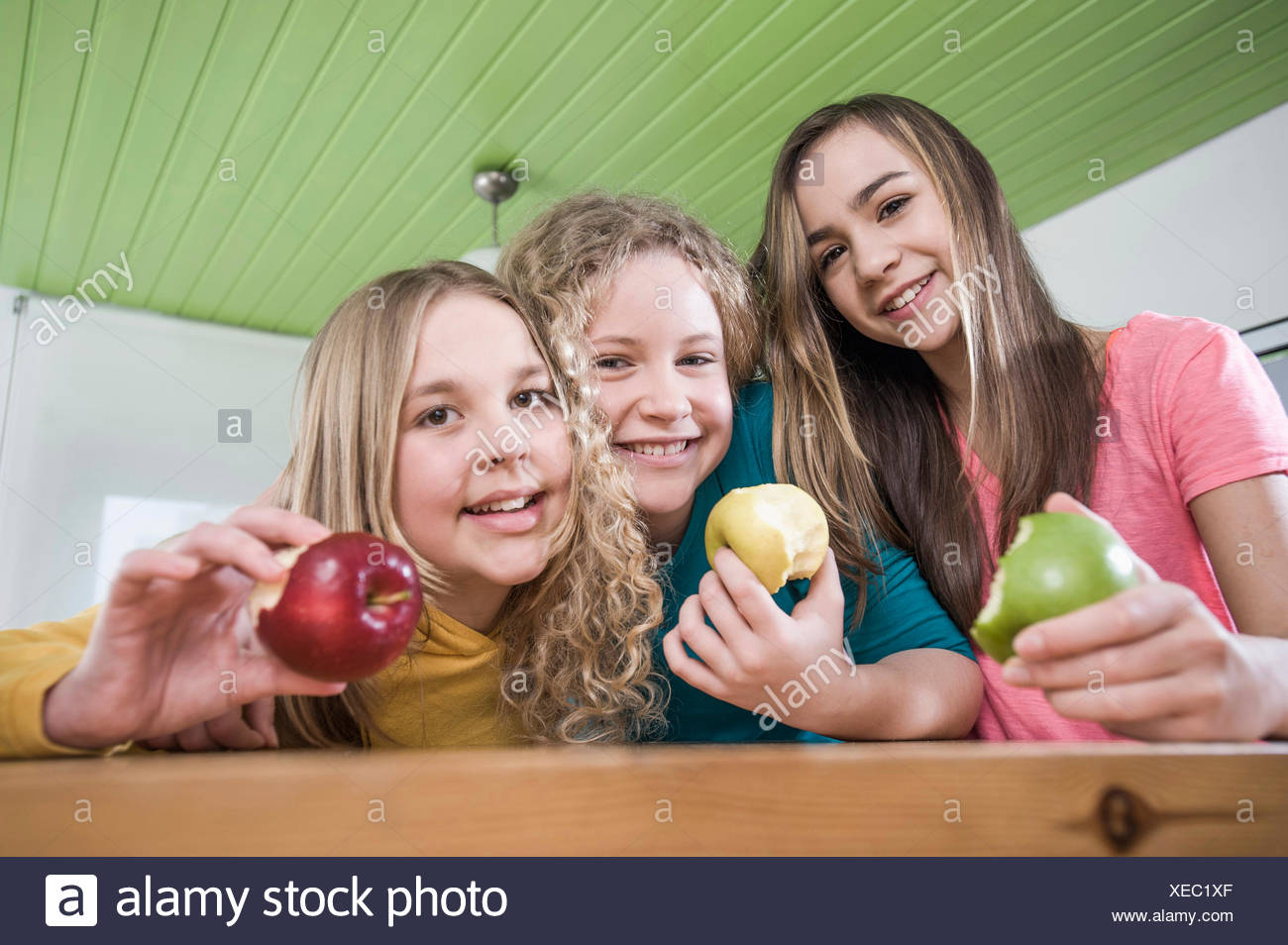 Girls in kitchen eating apples - Stock Image