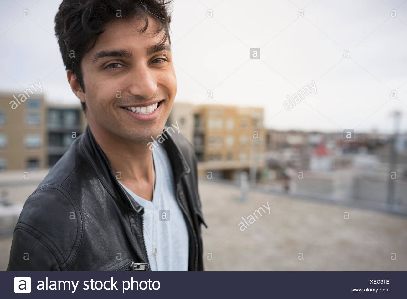 Portrait of smiling man on urban rooftop - Stock Image