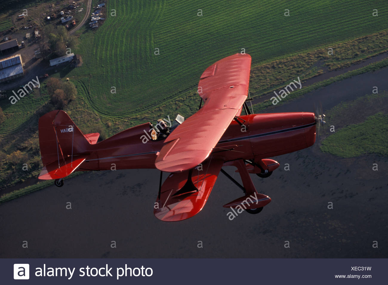 Red Bi wing Plane Flying Over Water And Farms - Stock Image