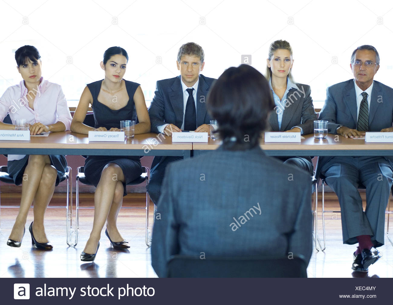 Executives sitting at conference table, looking at man in foreground - Stock Image
