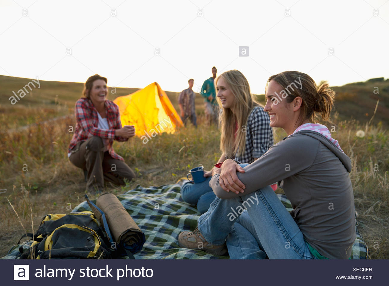 Friends sharing a laugh while camping. - Stock Image