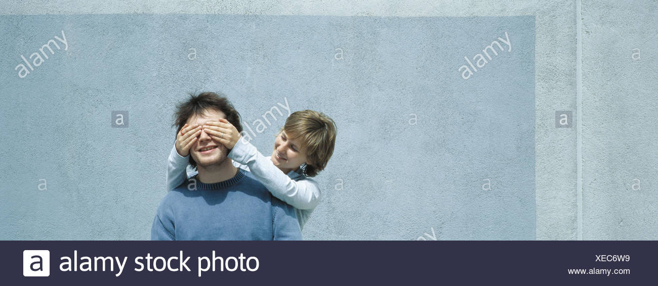Young woman covering young man's eyes Stock Photo