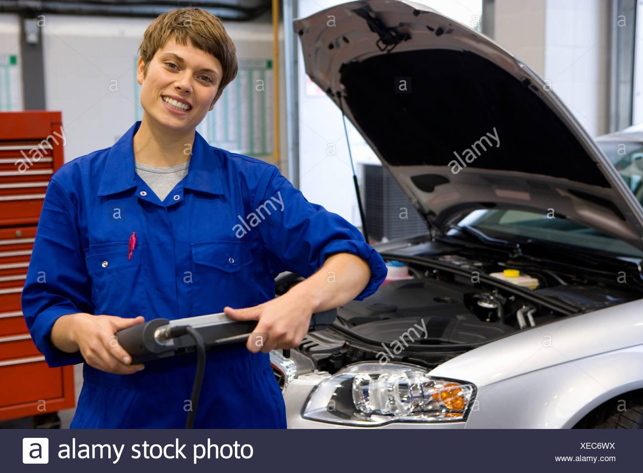Female mechanic with electronic diagnostics device, portrait - Stock Image