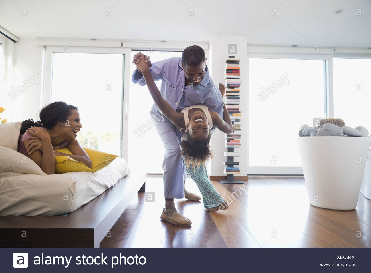 Cheerful father and daughter dancing in bedroom - Stock Image