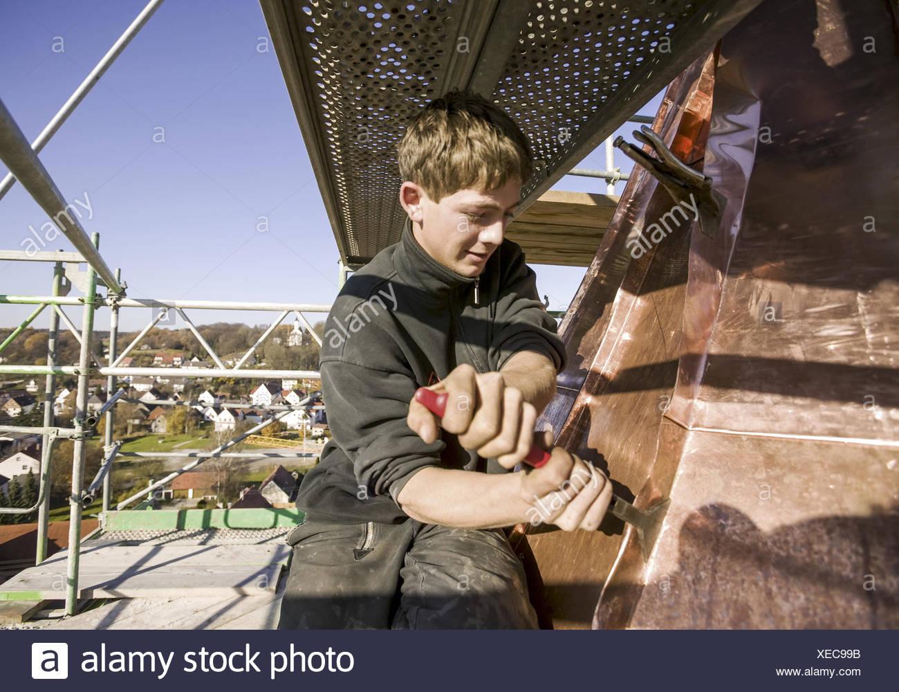 Spengler, Lehrling arbeitet mit Stemmeisen an Kupferdach eines Kirchturms (model-released) Stock Photo