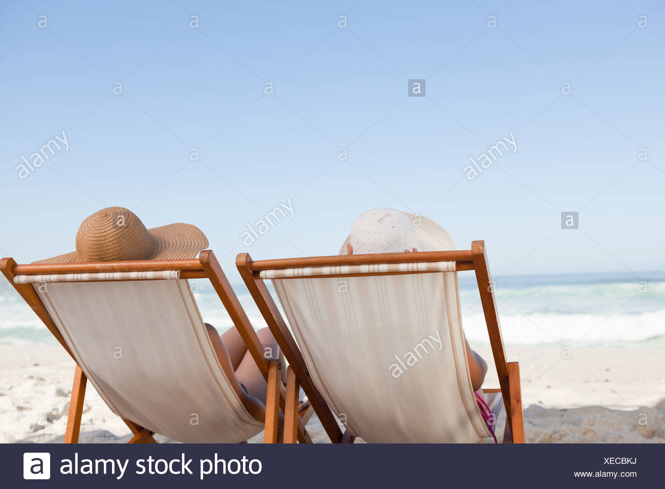 Young Women Sunbathing While Sitting On Deck Chairs On The Beach