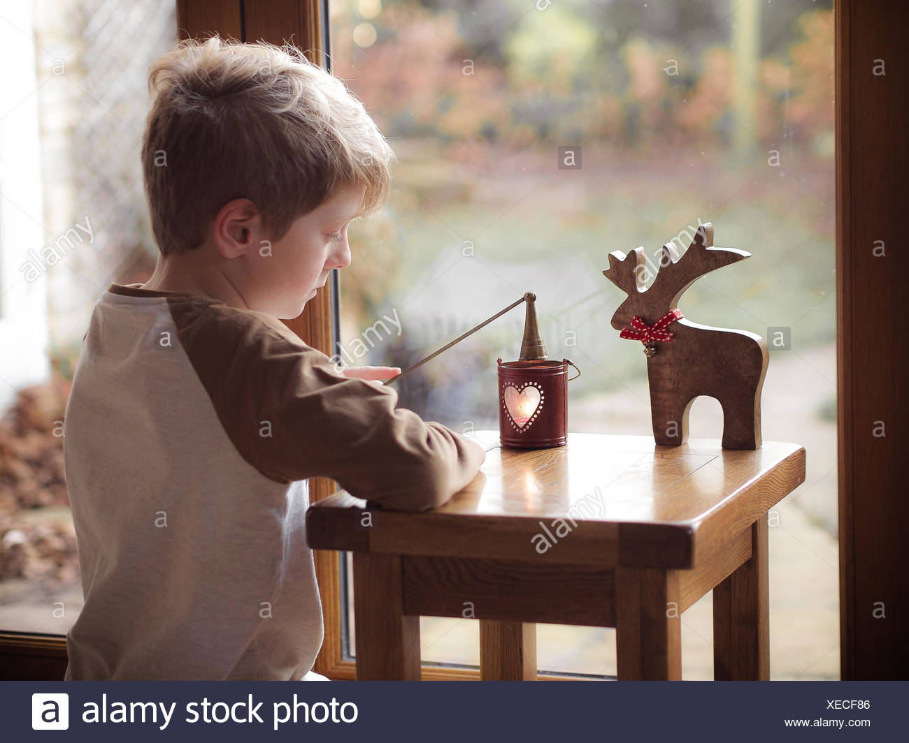 Boy (6-7) putting candle out of lantern - Stock Image