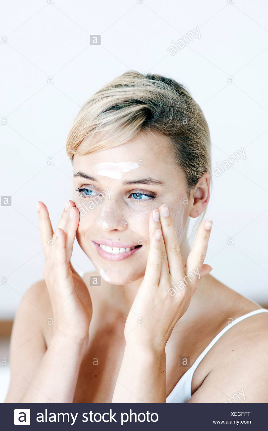 Female with fair hair tied at the back, applying face cream to her cheeks with both hands, smiling - Stock Image