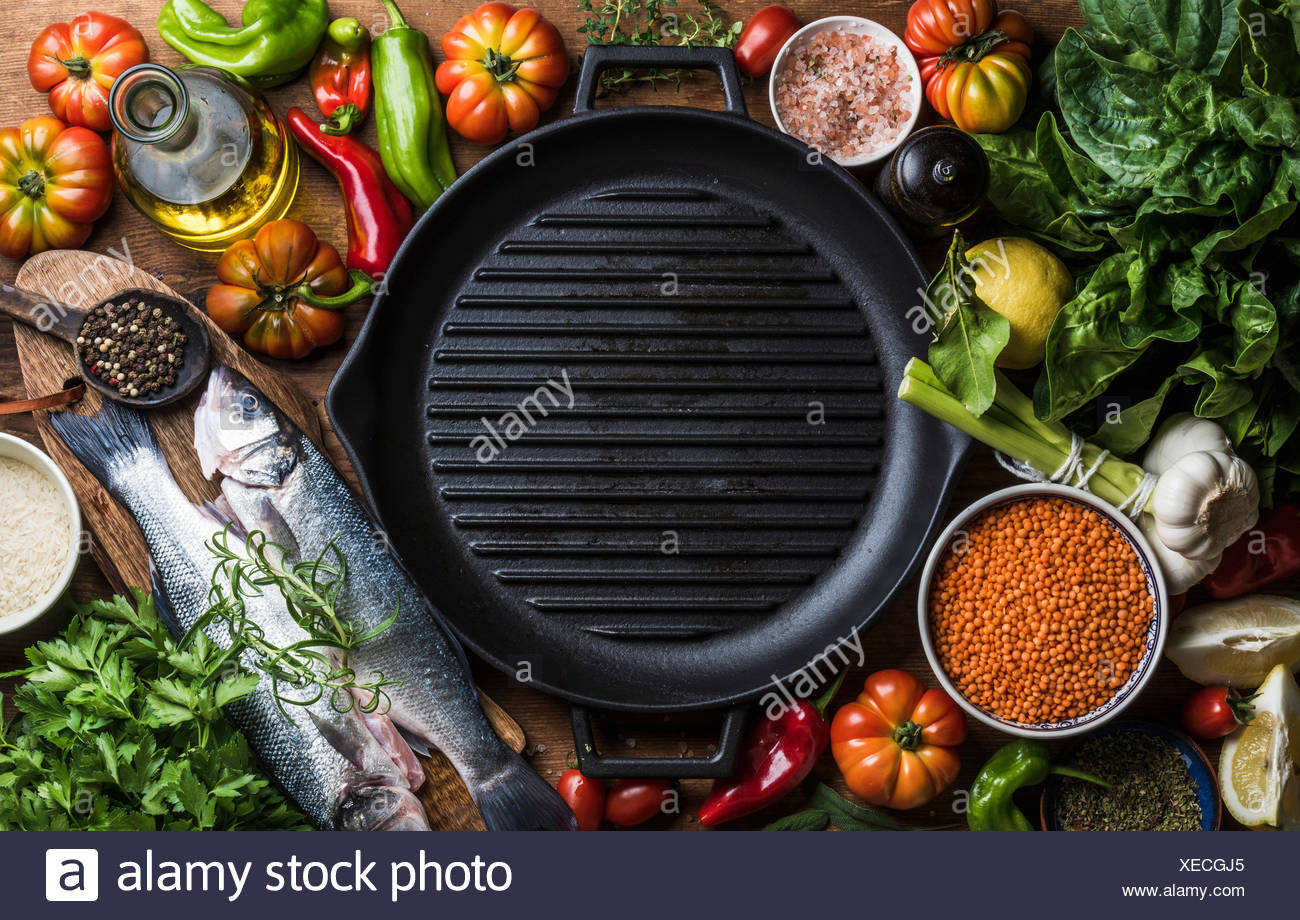 Ingredients for cooking healthy dinner. Raw uncooked seabass fish with vegetables, grains, rice, herbs and spices and black gril - Stock Image