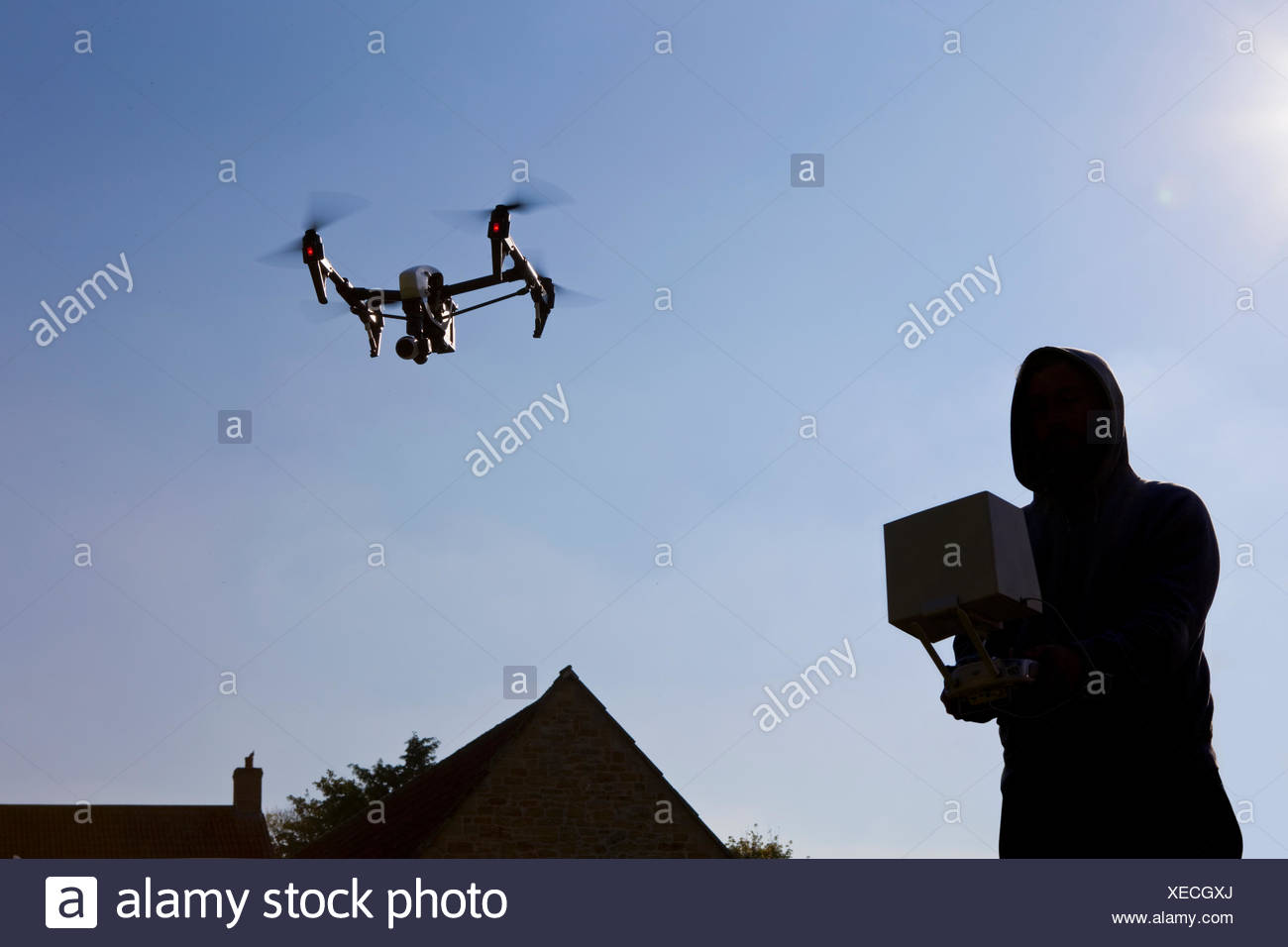 Man operating surveillance drone in blue sky - Stock Image