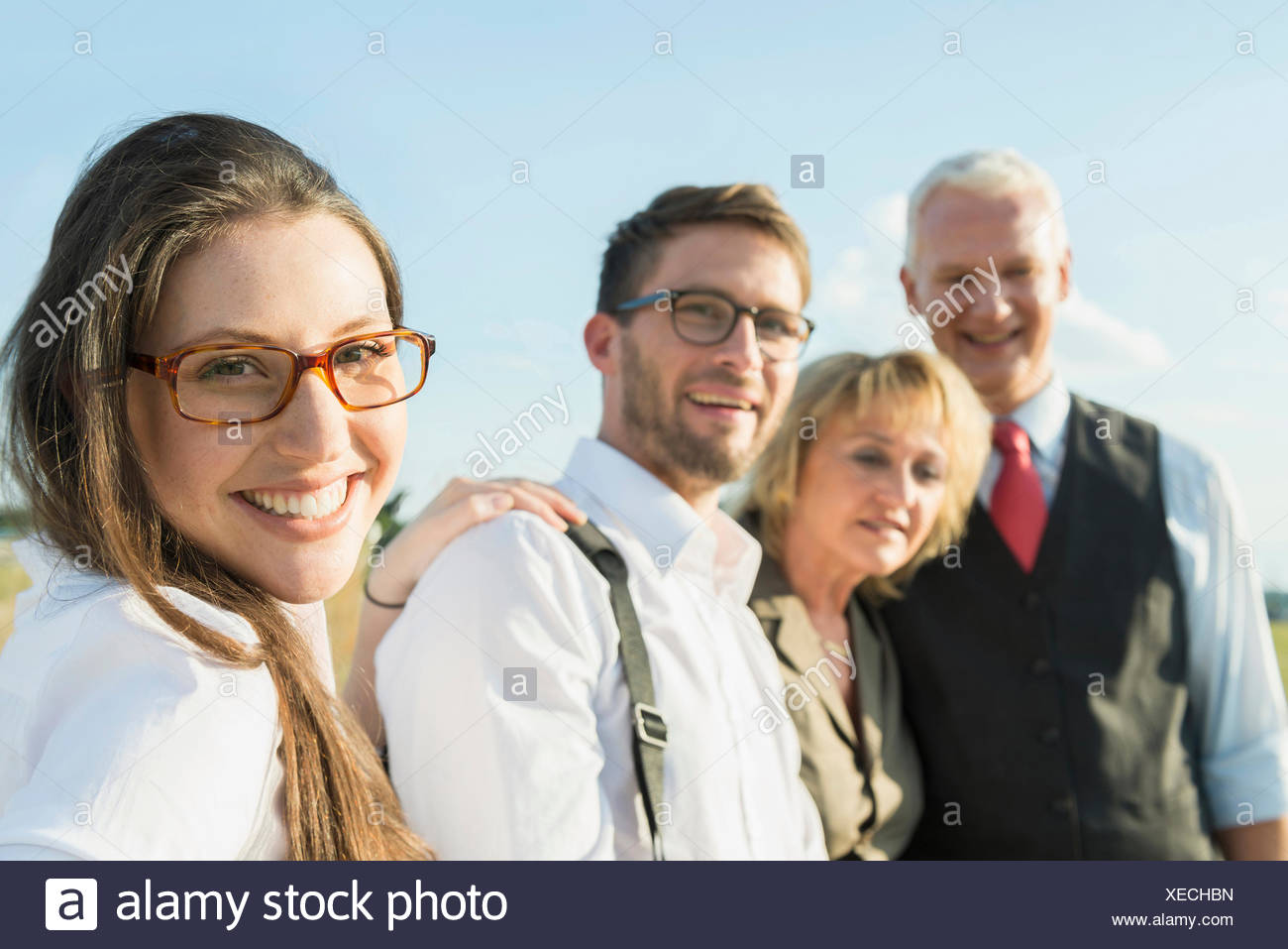 Smiling young woman with three other people outdoors, portrait - Stock Image