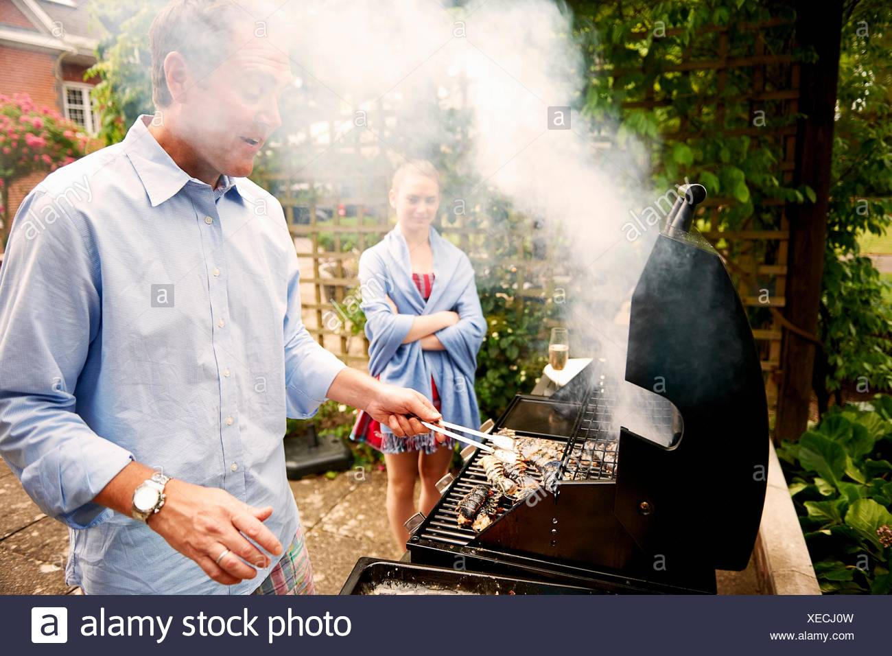 Daughter watching father cook sea food on barbecue - Stock Image