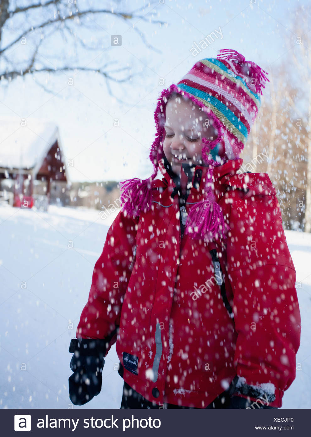 Girl (6-7) standing in snow fall Stock Photo