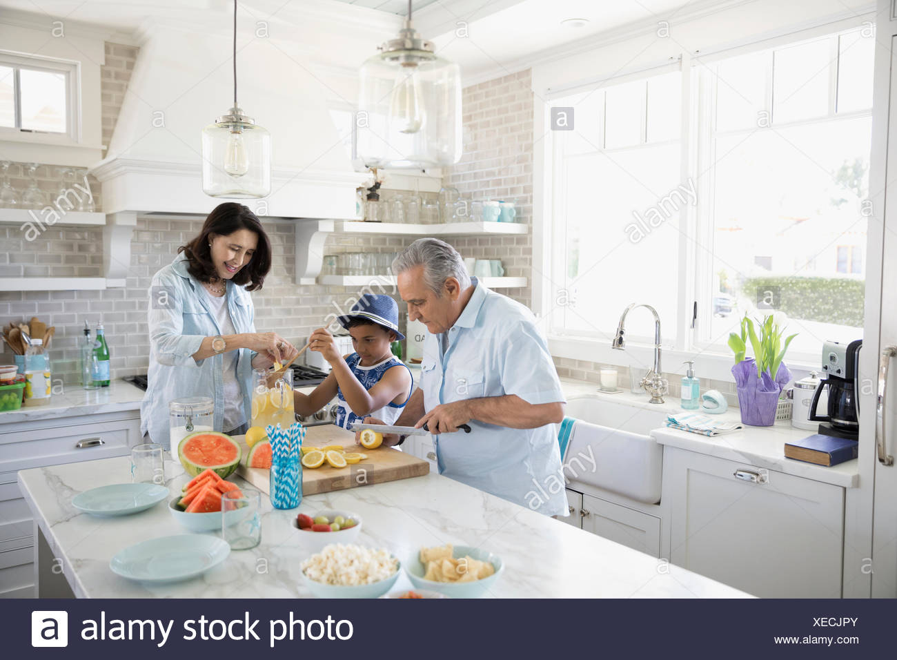Grandparents and grandson making lemonade in beach house kitchen - Stock Image