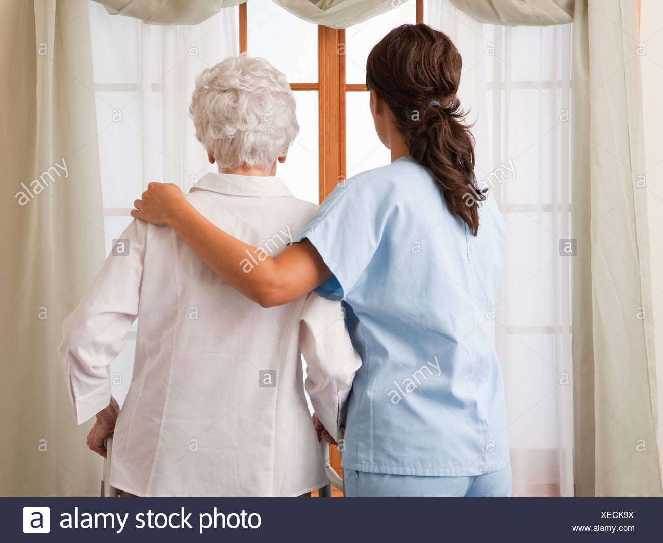 USA, Illinois, Metamora, Rear view of female nurse and senior woman looking through window - Stock Image