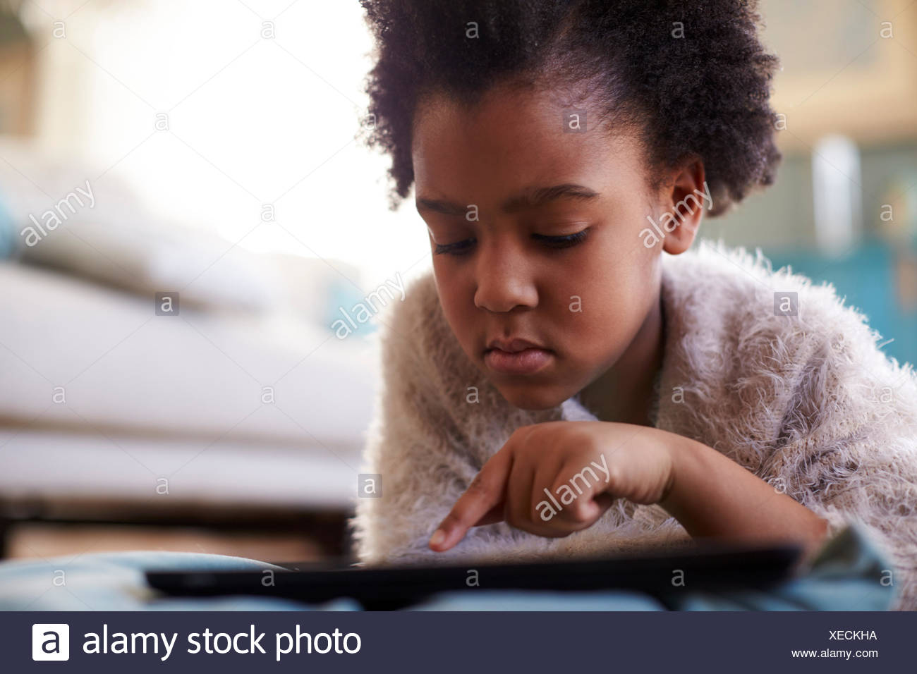 Young Girl Using Digital Tablet At Home - Stock Image