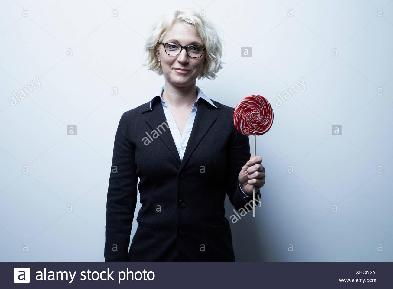 Studio portrait of blond businesswoman with red lollipop - Stock Image