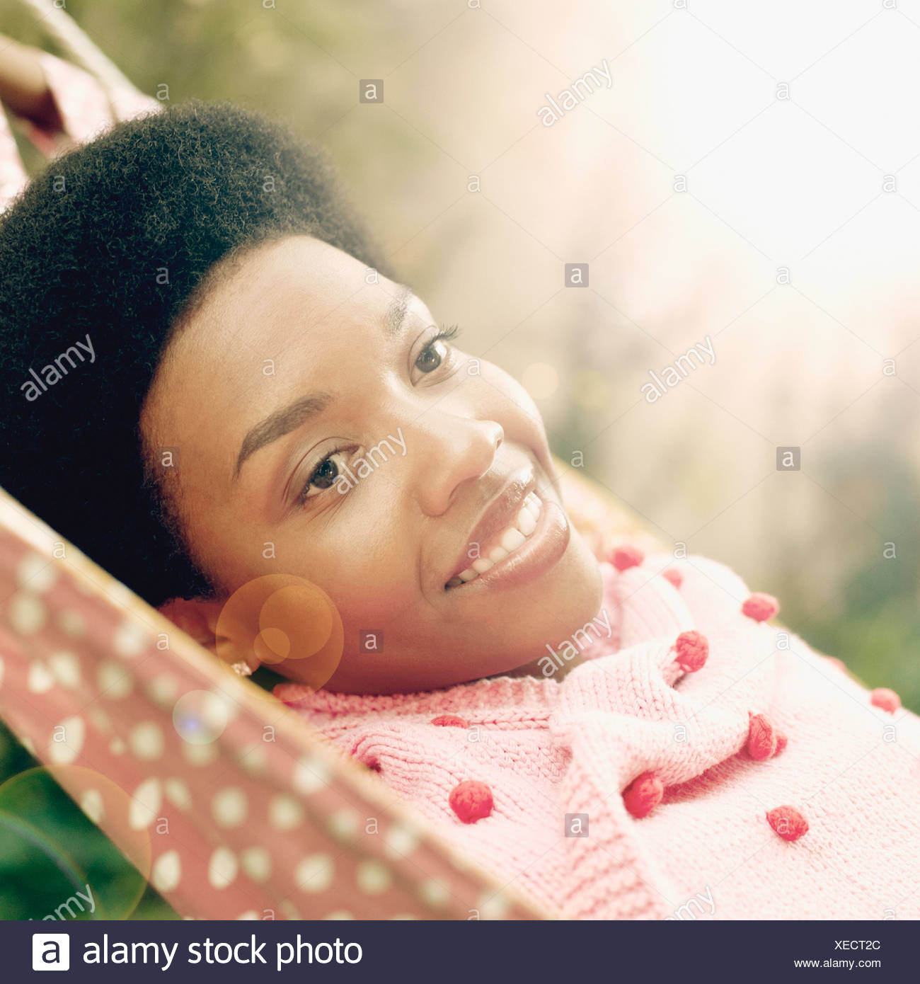 Close-up of a young woman smiling and lying in a hammock - Stock Image