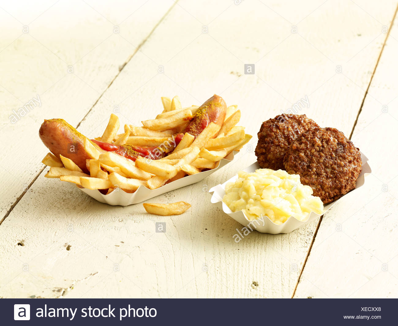Curry sausage with French fries, two meatballs and mashed potatoes on wooden table Stock Photo