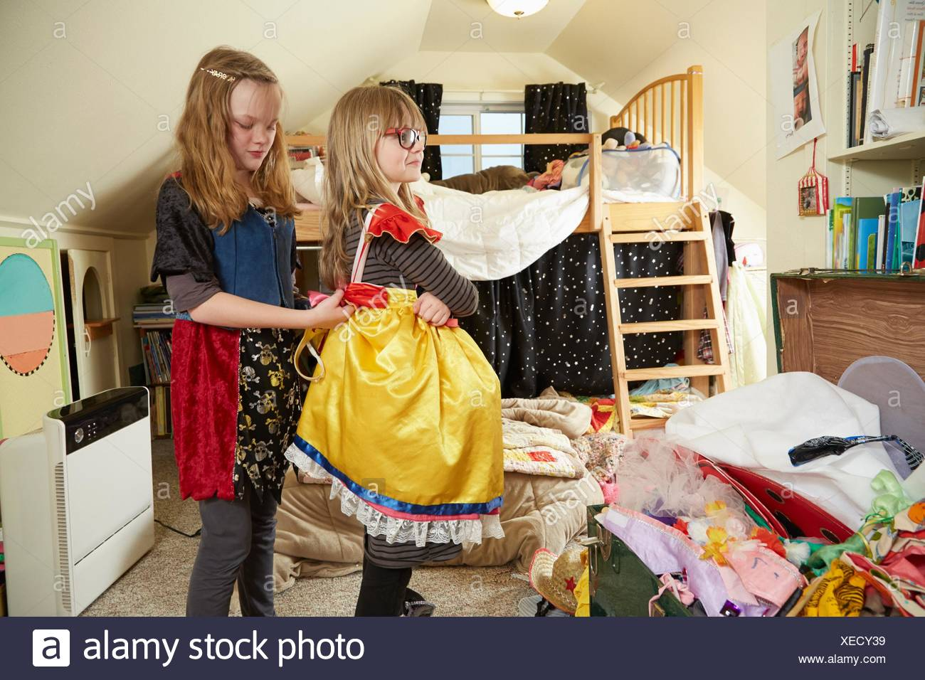 Two sisters playing dress up, One helping the other fasten dress - Stock Image