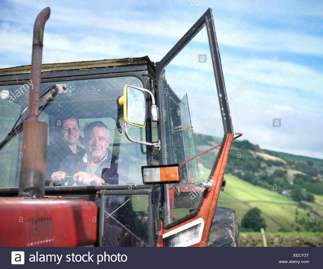 Farmer and son in tractor cab, portrait - Stock Image