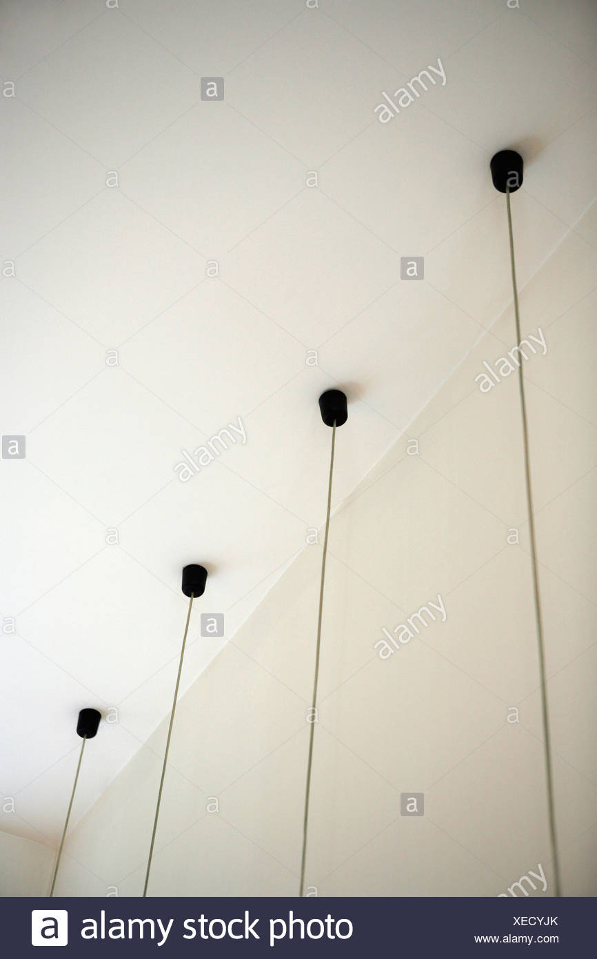 Four light fixtures with cables hanging down from ceiling - Stock Image