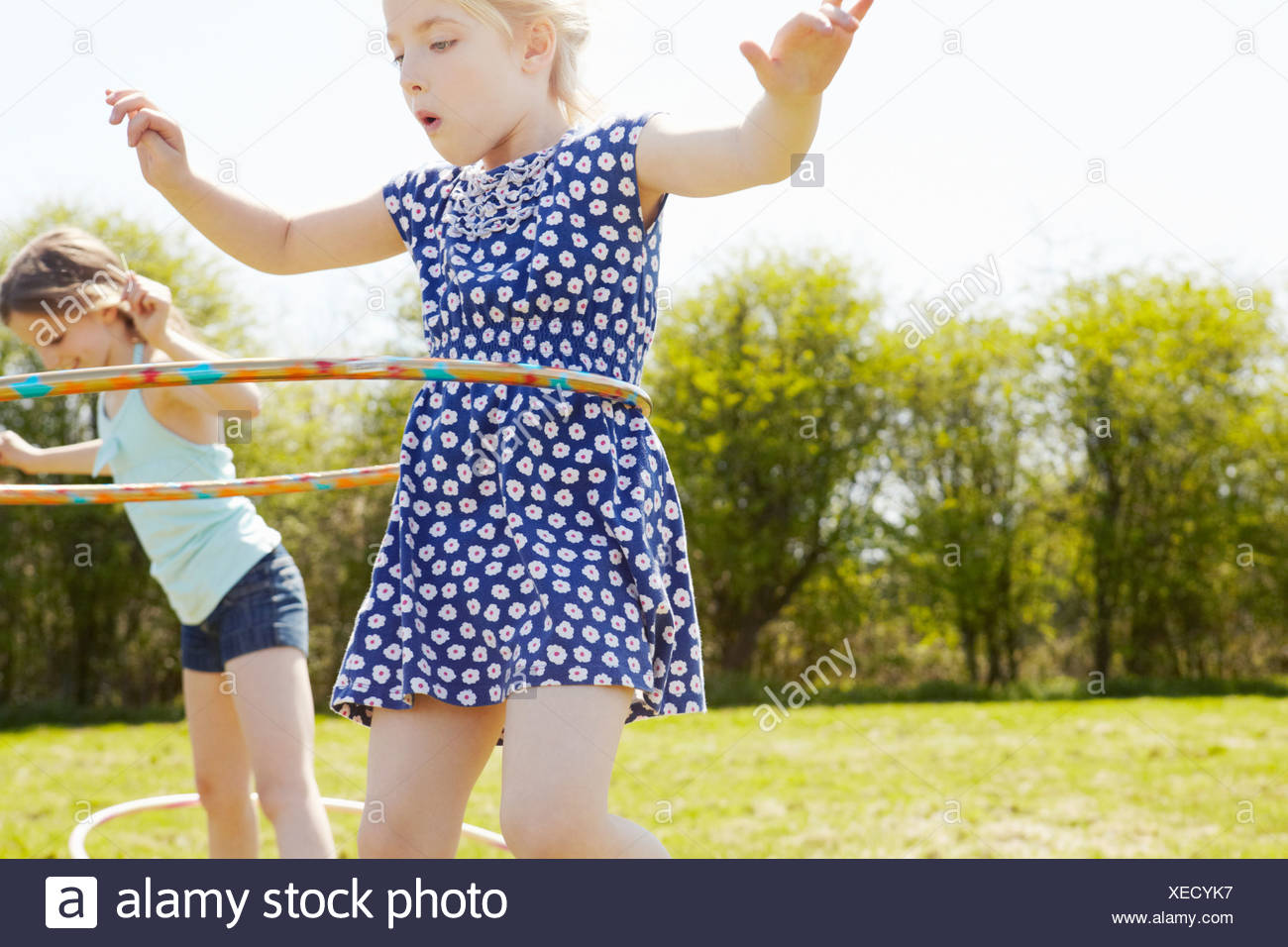 Low angle view of two girls playing with plastic hoops Stock Photo