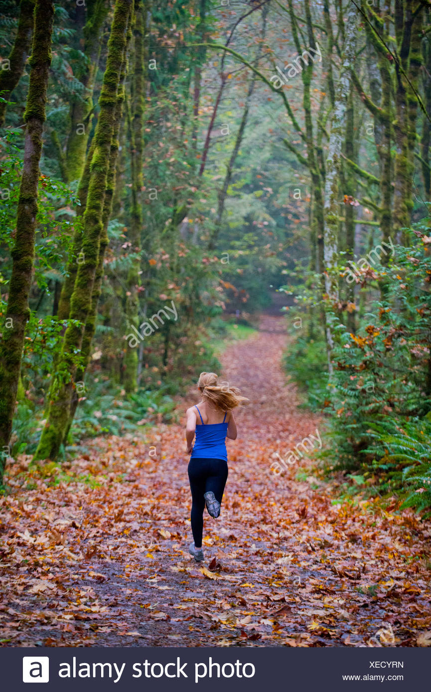 Girl jogging in forest Stock Photo