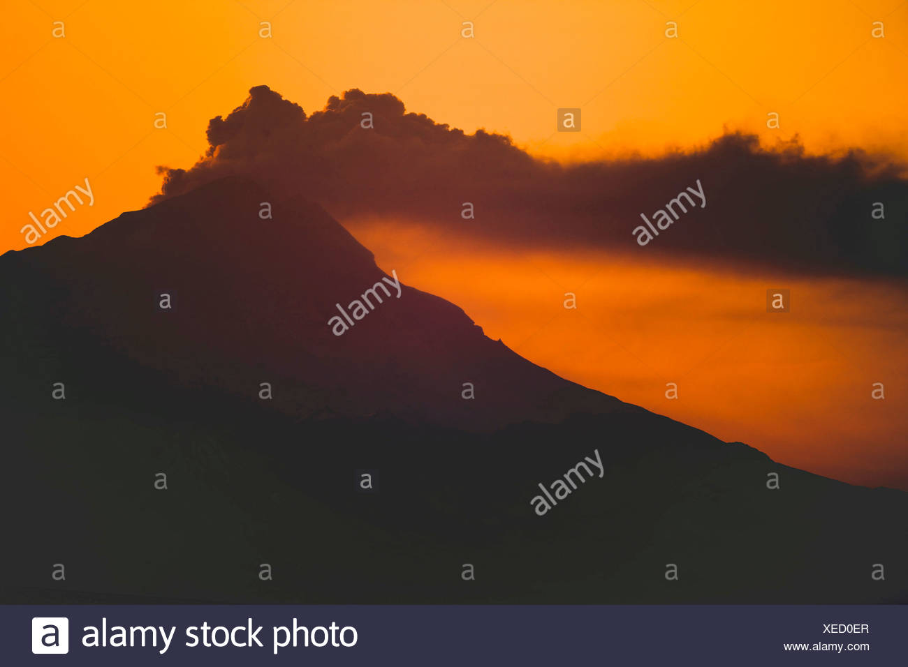 Alaska. Mt. Redoubt emitting steam and ash at sunset, as viewed from Kenai. Stock Photo