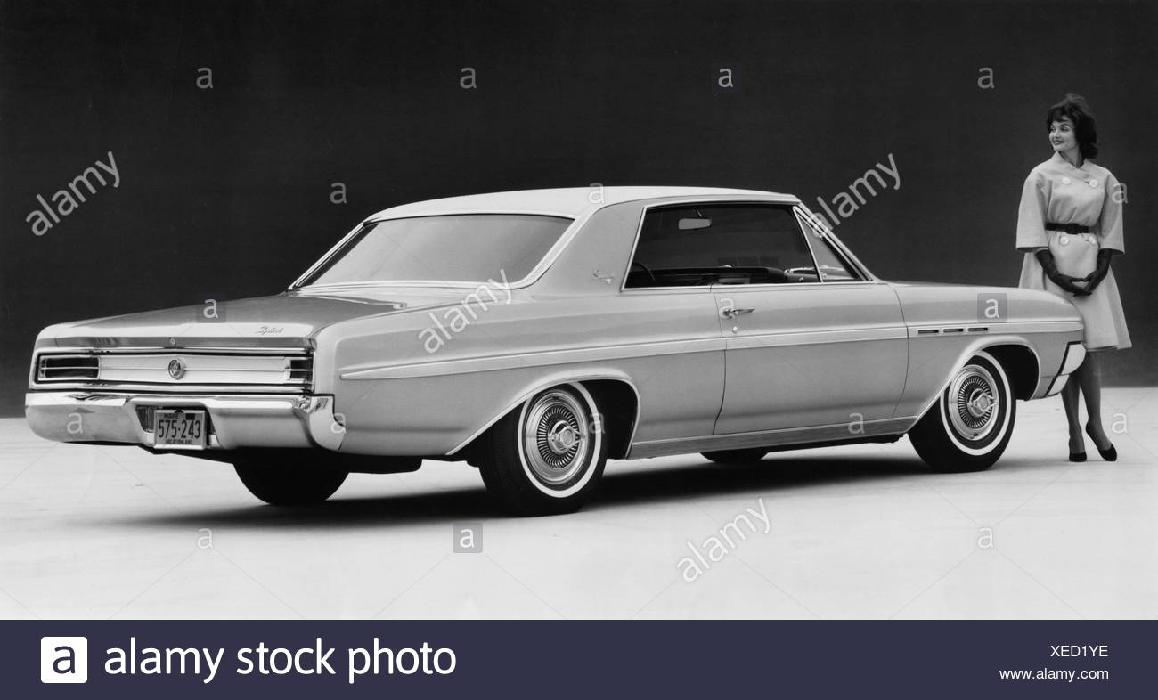 Young woman standing near 1964 Buick Skylark coupe - Stock Image