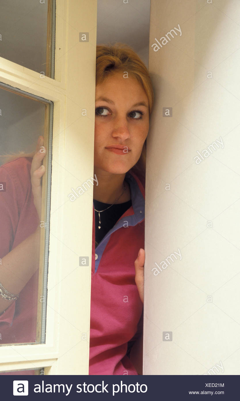 young woman looking suspiciously out of window Stock Photo