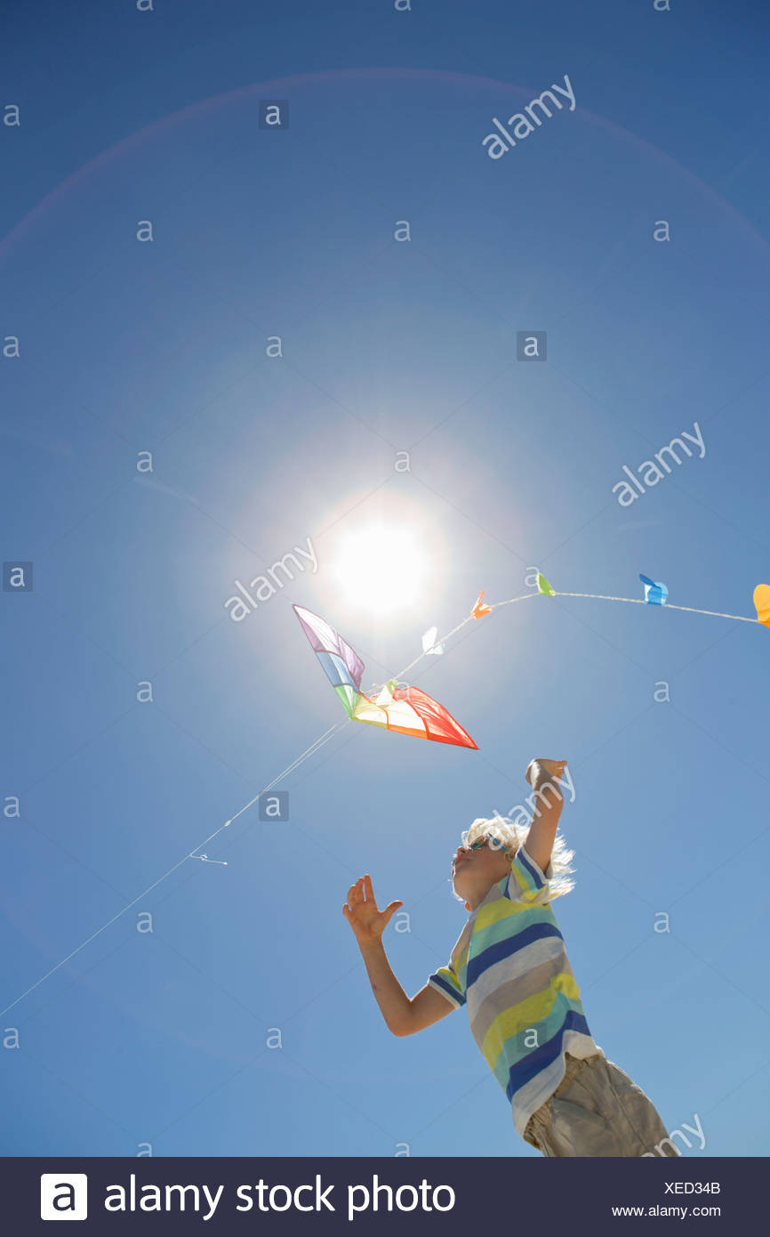 Boy jumping and reaching for kite under sun in blue sky - Stock Image