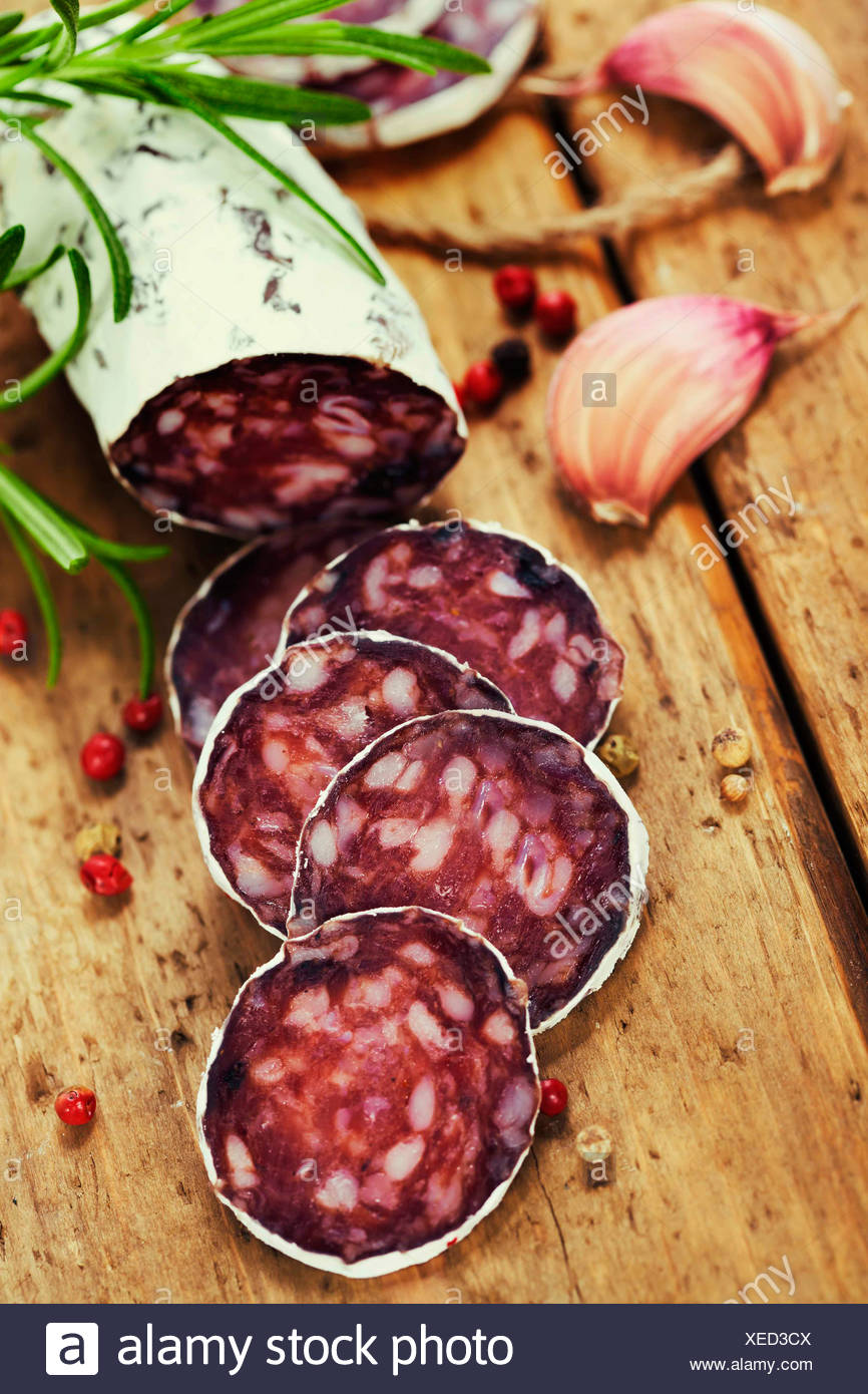 Close-up traditional sliced meat sausage salami on wooden board with head of garlic and green herbs - Stock Image