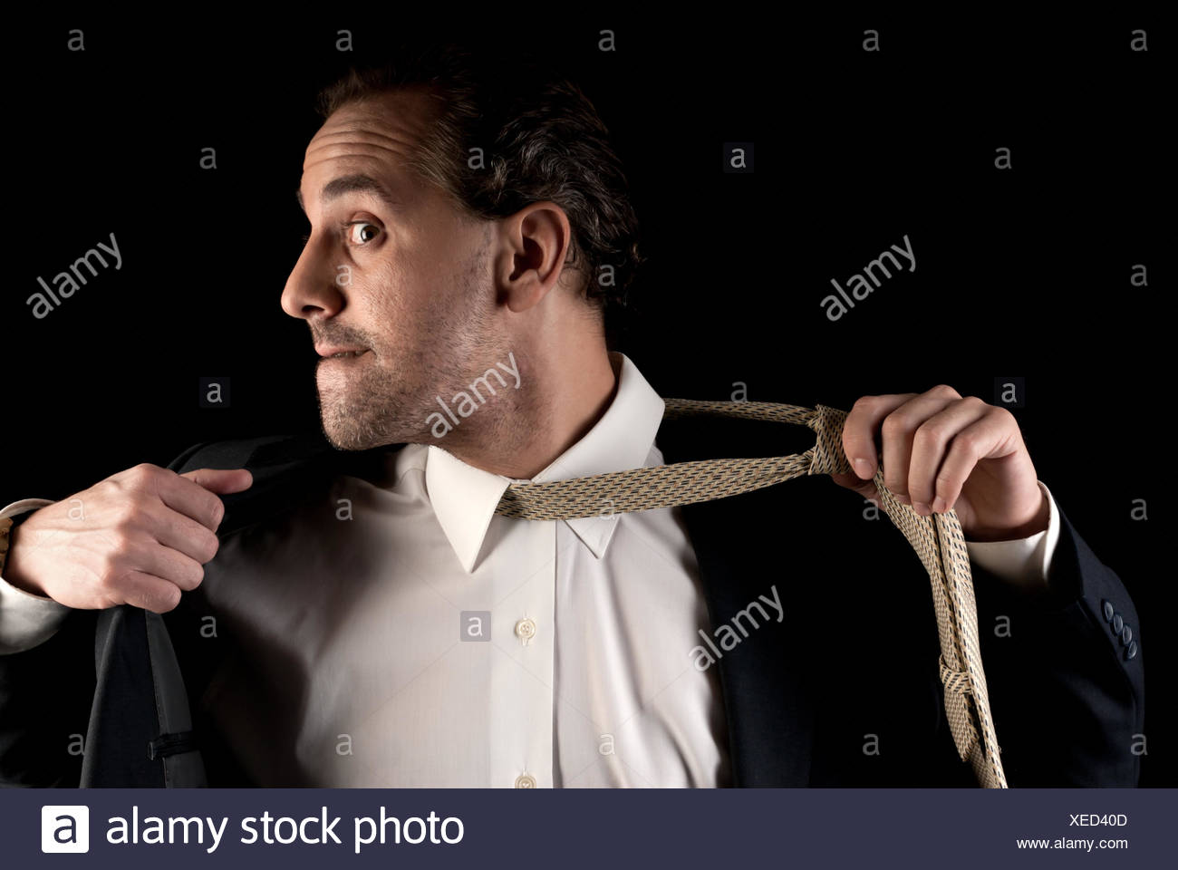 Adult businessman stressed pulling off tie on dark background - Stock Image