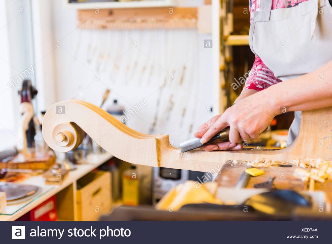 Violin maker making violins in production studio - Stock Image