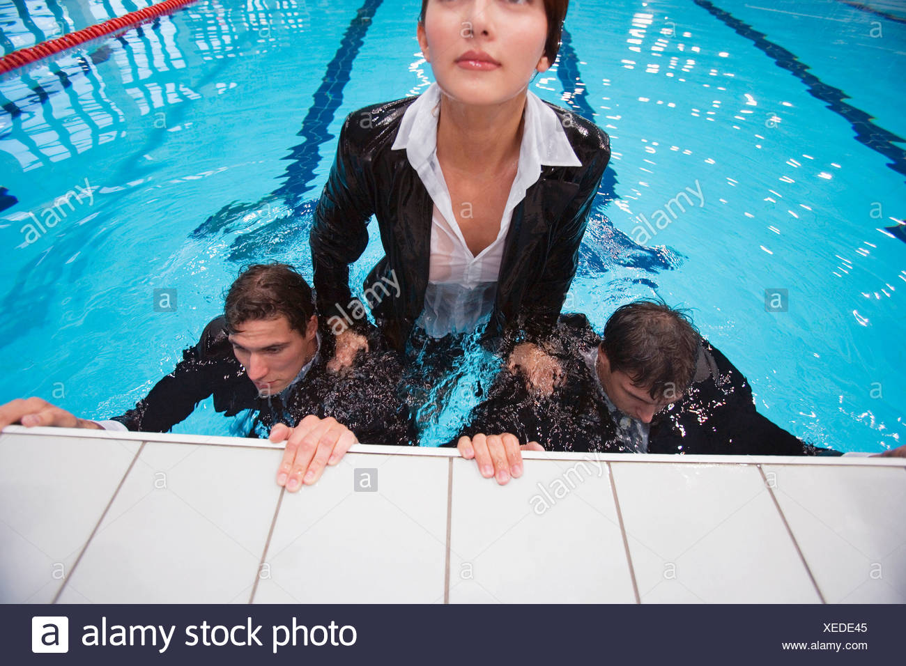 Woman leaning on men in water - Stock Image