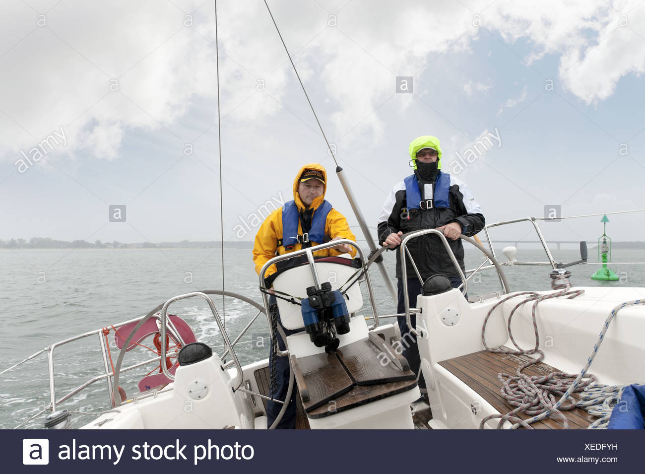 2 men standing at the stern of a yacht Stock Photo
