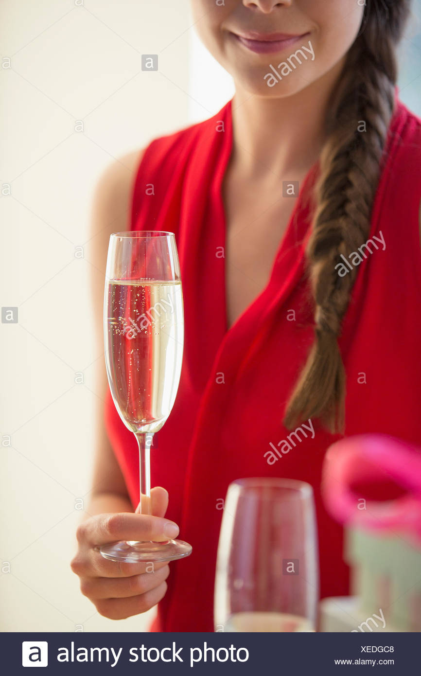 Woman holding champagne flute - Stock Image