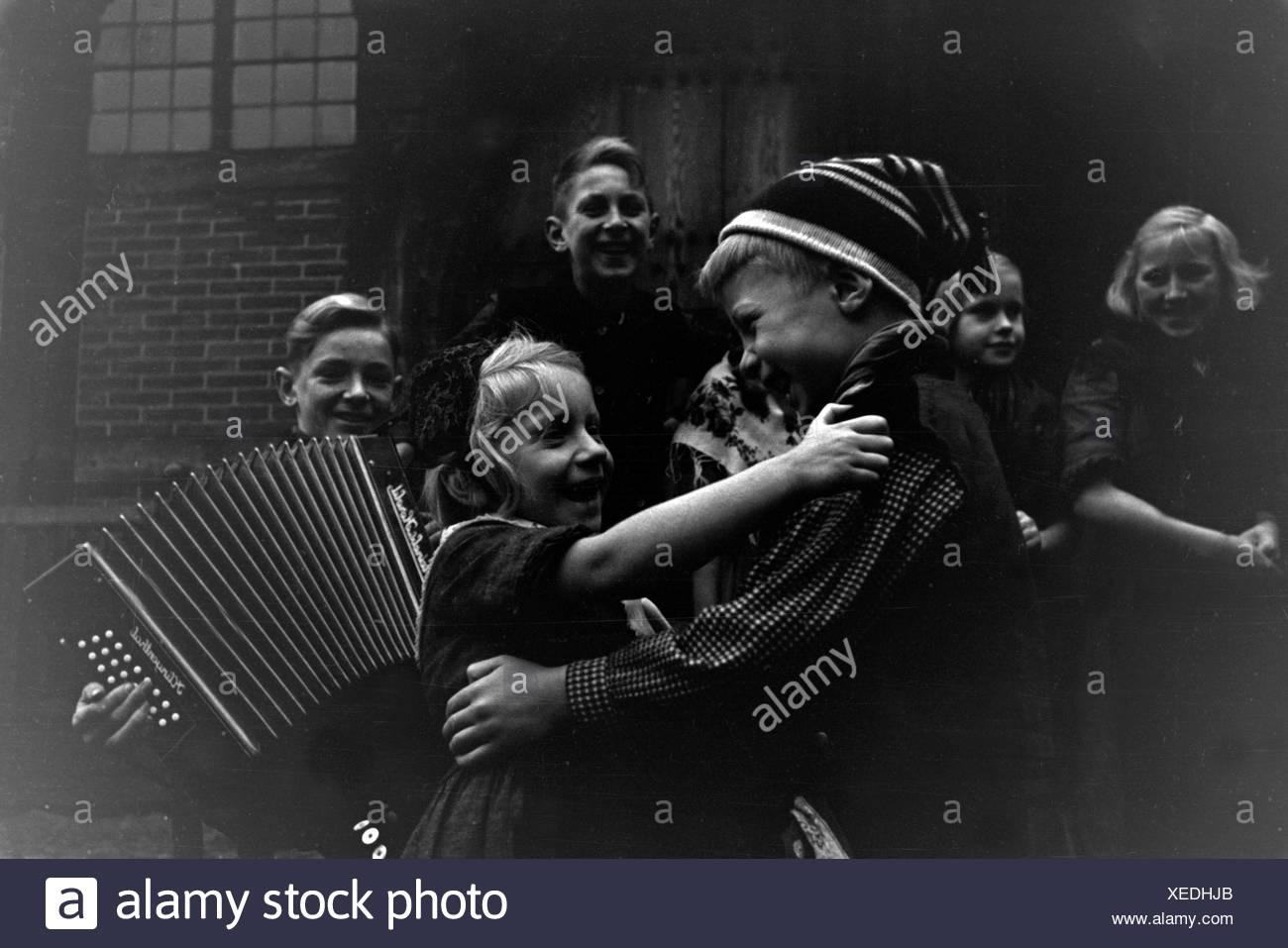 Kinder tanzen in der Tracht der Gegend um Ammerland bei Bad Zwischenahn im Oldenburger Land, Deutschland 1930er Jahre. Children dancing in traditional costume of Ammerland near Bad Zwischenahn at the Oldenburg area, Germany 1930s - Stock Image