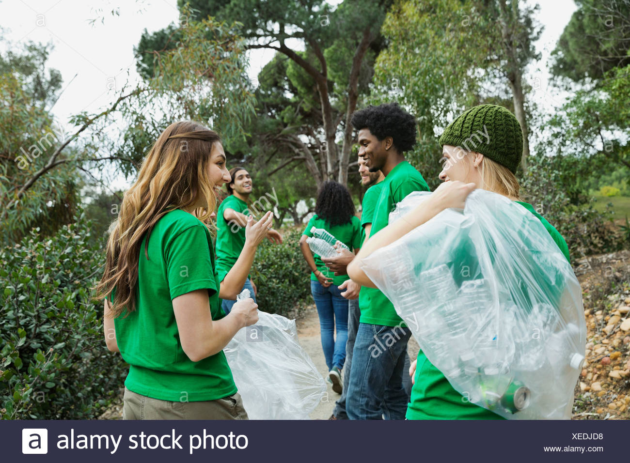 Team of environmentalists with empty bottles and plastic bags in park - Stock Image